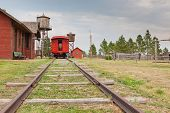 stock photo of caboose  - Looking down the tracks at a bright red caboose of a train pulled in to an old west style station with a water tower and telegraph wires - JPG