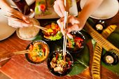 stock photo of chopsticks  - Young people eating in a Thai restaurant - JPG