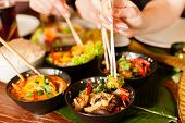 stock photo of sate  - Young people eating in a Thai restaurant - JPG