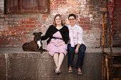 image of queer  - Smiling female friends with dog on old loading dock - JPG