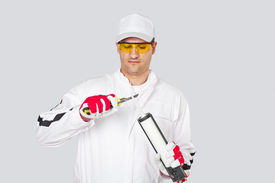 stock photo of mortar-joint  - Nice looking worker with knife remove cut cap sealant silicon gun - JPG