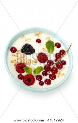 healthy breakfast: bowl of cerial with yogurt or milk, fresh berries and mint over white