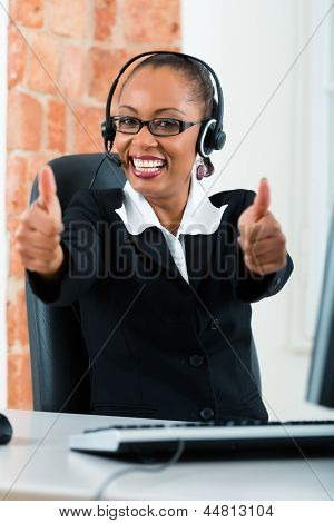Young businesswoman or secretary working in her Office, she sitting on the desk in front of the window and working on a computer with a headset, she has a customer pitch