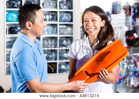 Asian customer in in a store or shop for divers, an employee helping putting on the harness