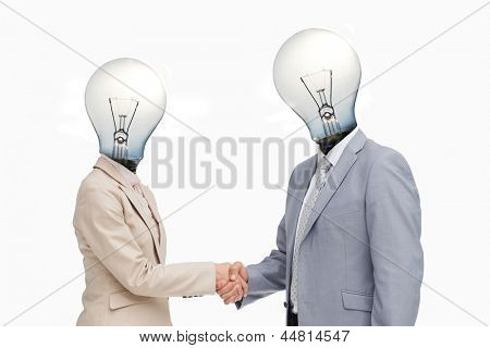 Business people with lightbulb heads greeting with a handshake against white background