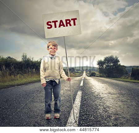 little child with with a sign on the road