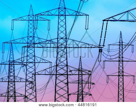 the mast of a high voltage transmission line for electricity before dark clouds.