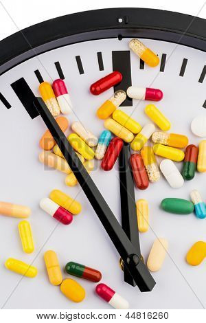 colorful capsules on a clock, symbolic photo for healthcare, health reform, congestion