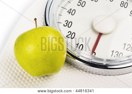 on a bathroom scale is an apple. symbolic photo for weight loss and healthy, vitamin-rich diet.