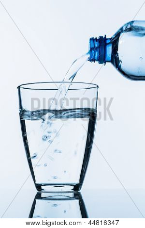 from a bottle of water being poured into a glass, symbolic photo for drinking water, supplies and consumables