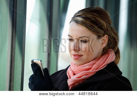 Pretty Blond Young Business Woman Using A Smartphone Wearing A Winter Coat Scarf And Gloves