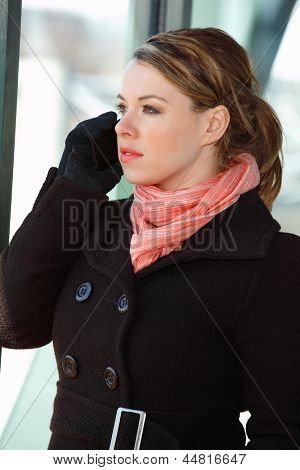 Pretty Blond Young Woman Looking Out Of An Airport Building Window Talking On A Cellphone Mobile