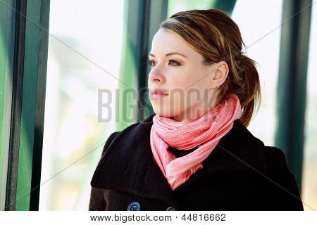 Pretty Blond Young Woman Looking Out Of An Airport Building Window