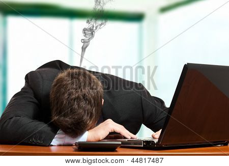 Collapsed businessman with smoke coming out from his head