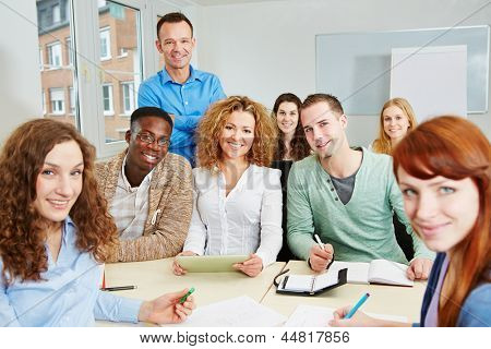 Teacher with his happy students in a college course classroom