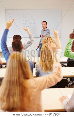 Students answering question in school class with teacher on whiteboard