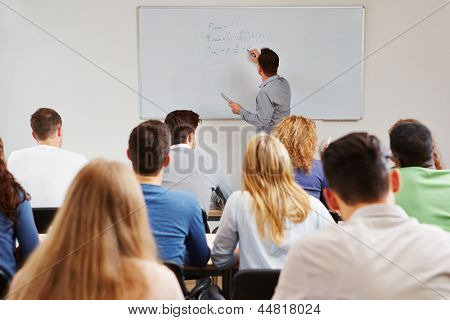 Teacher on whiteboard in class teaching business studies in university