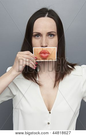 young woman covering with lips picture. concept photo over grey background