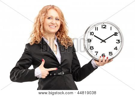 A blond mature woman standing and pointing on a wall clock, isolated on white background