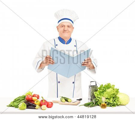 A mature chef reading a cookbook during a preparation of fresh salad isolated on white background