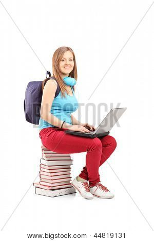 A smiling student with backpack working on a laptop and sitting on pile of books, isolated on white background