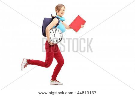 Full length portrait of a female student with clock late for class, isolated on white background