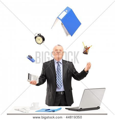 Mature businessman juggling in his office, isolated on white background