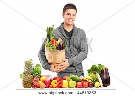 Handsome young man with a bag of groceries standing behind a pile of fruits and vegetables, isolated on white background
