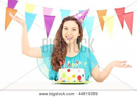 A smiling birthday female with a party hat posing isolated against white background