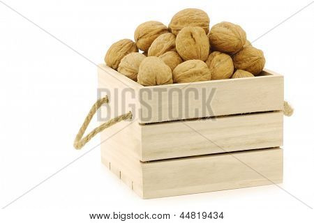 fresh walnuts in a wooden box with rope handles on a white background