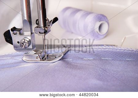 Sewing Process Of Blue Cloth On The Machine And Two Bobbins