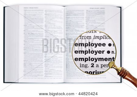 A magnifying glass held over a dictionary looking at the words Employee, Employer and Employment enlarged