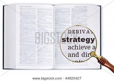 A magnifying glass held over a dictionary looking at the word Strategy enlarged