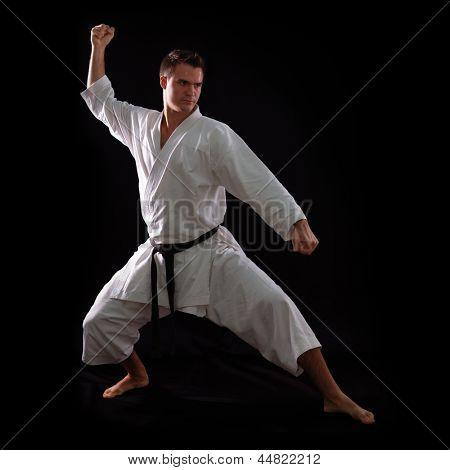 karate man with black belt posing, champion of the world on black background studio shot