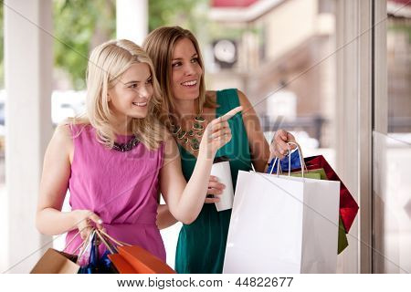 Two pretty women windows shopping in a down town city