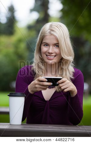 Portrait of a smiling woman using a mobile phone in park
