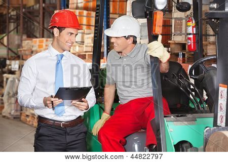 Supervisor communicating with forklift driver at warehouse