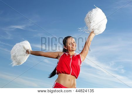 Young beautiful female cheerleader in uniform jumping high