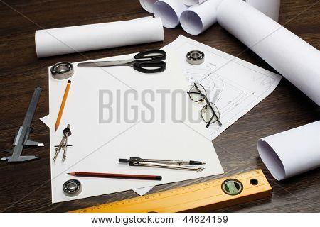 Herramientas y papeles con dibujos sobre la mesa
