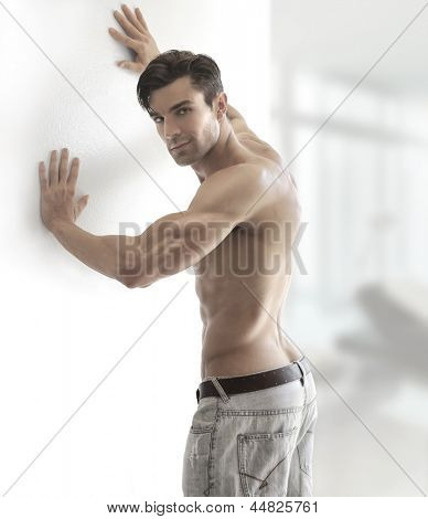 Portrait of a sexy muscular shirtless man turning in bright modern setting with copy space