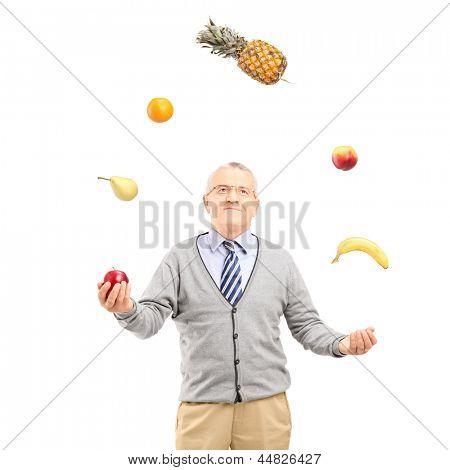 A mature man juggling fruits isolated on white background