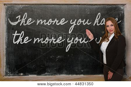 Teacher Showing The More You Have, The More You Want On Blackboard