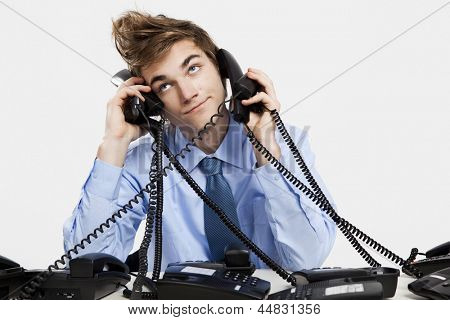 Young man sitting in the office and answering several phones at the same time