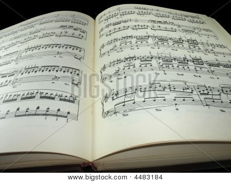 Old Vintage Sheet Music Book Over Black Background