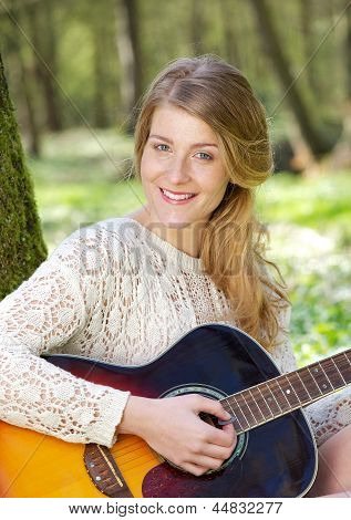 Portrait Of An Attractive Young Woman Smiling With Guitar Outdoors