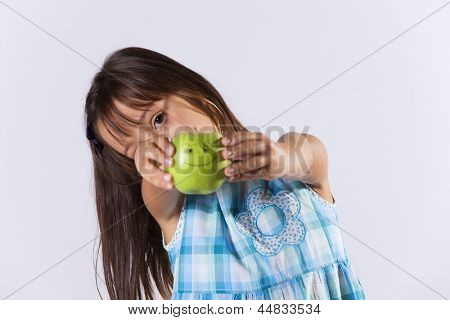 Little girl showing a green apple with a smile