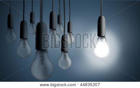 One bulb lighting up on blue background
