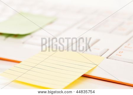 Postit notes attached to a white keyboard