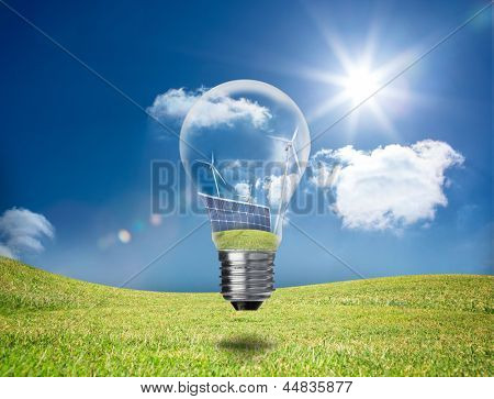 Light bulb showing solar panels and turbines hovering in a green field in the sunshine