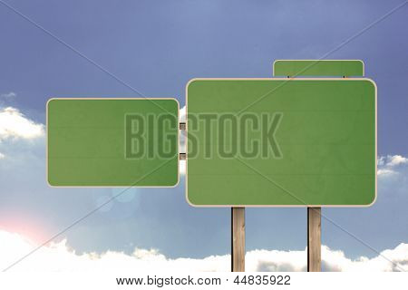 Blank green road sign against a cloudy sky